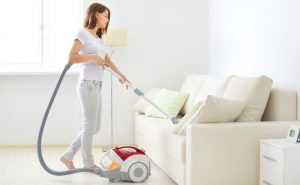 Lady cleaning cushion covers with vacuum cleaner