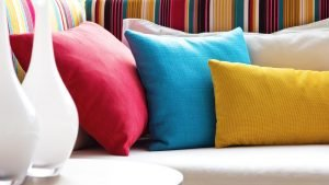 Colourful cushions alongside some vases