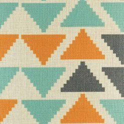 Close up view of orange teal and dark grey triangles on cushion