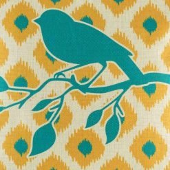 Close up showing bird sitting on branch on cushion cover