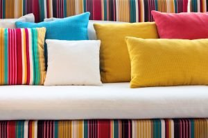 Bright colourful designer cushion covers on a very bright sofa with lines