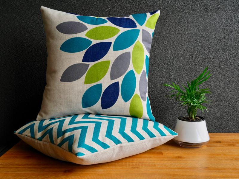 Blue and teal coloured cushions sitting on a wooden table with pot plant to the right