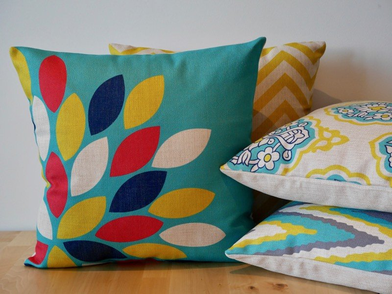 A stack of brightly coloured cushion sitting on a wooden surface