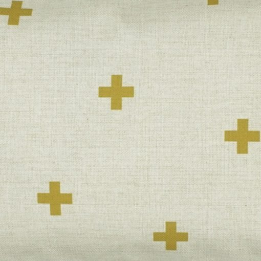 Close up of rectangular linen cushion with gold cross design