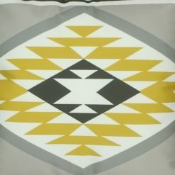 Close up of yellow, grey and white velvet cushion with Aztec print