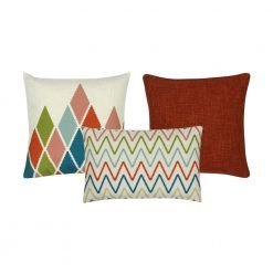 A collection of 3 cushion covers with burnt orange and white colours and in zigzag and diamond patterns.