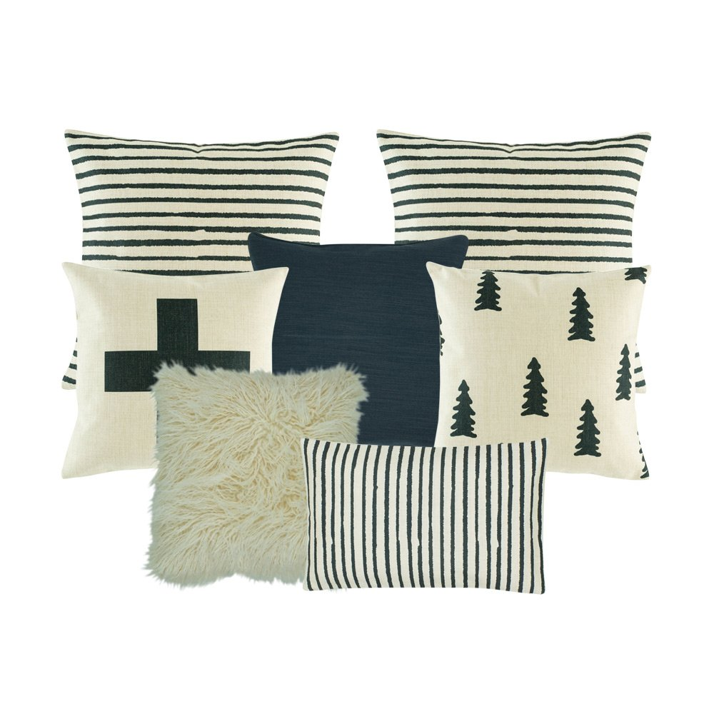 A set of dark blue and white cushions with stripes, tree and cross designs
