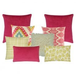 A mix of square and rectangular cushions in yellow and fuchsia colours and with diamond and leaf designs