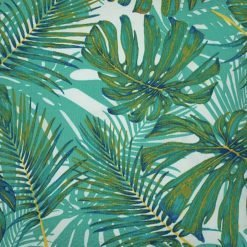 Close up photo of outdoor cushion cover with leaves in teal colour