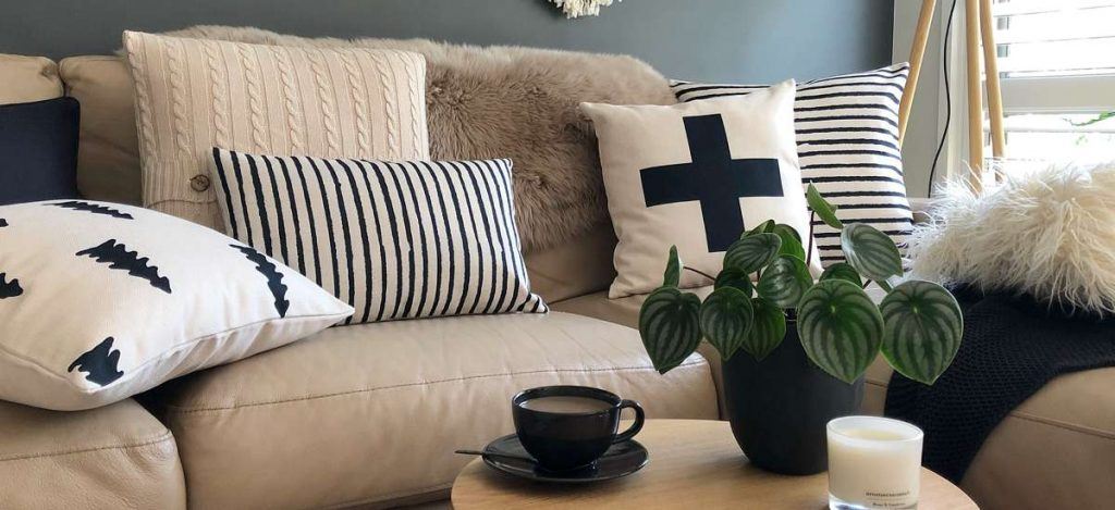 Styled scene with black and white cushions of different prints, textures and sizes