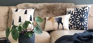 Living room with beige sofa and Scandi styled cushions set up against a fur throw