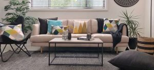 A scene styled with urban modern decor including blue patterned cushions and black chair