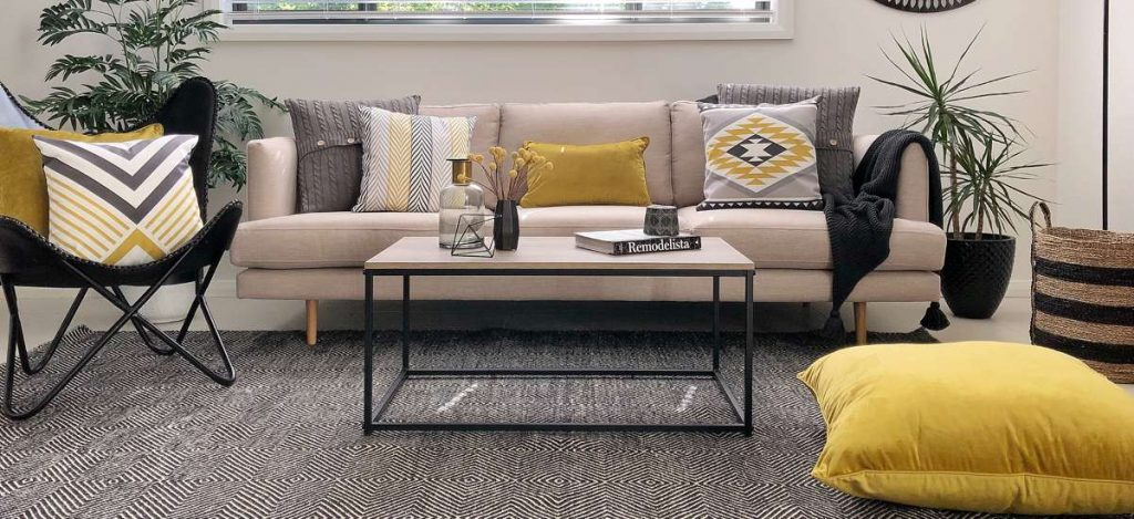 Living room scene styled in urban modern look including yellow and grey cushions on a cream sofa and a large velvet floor cushion in the foreground