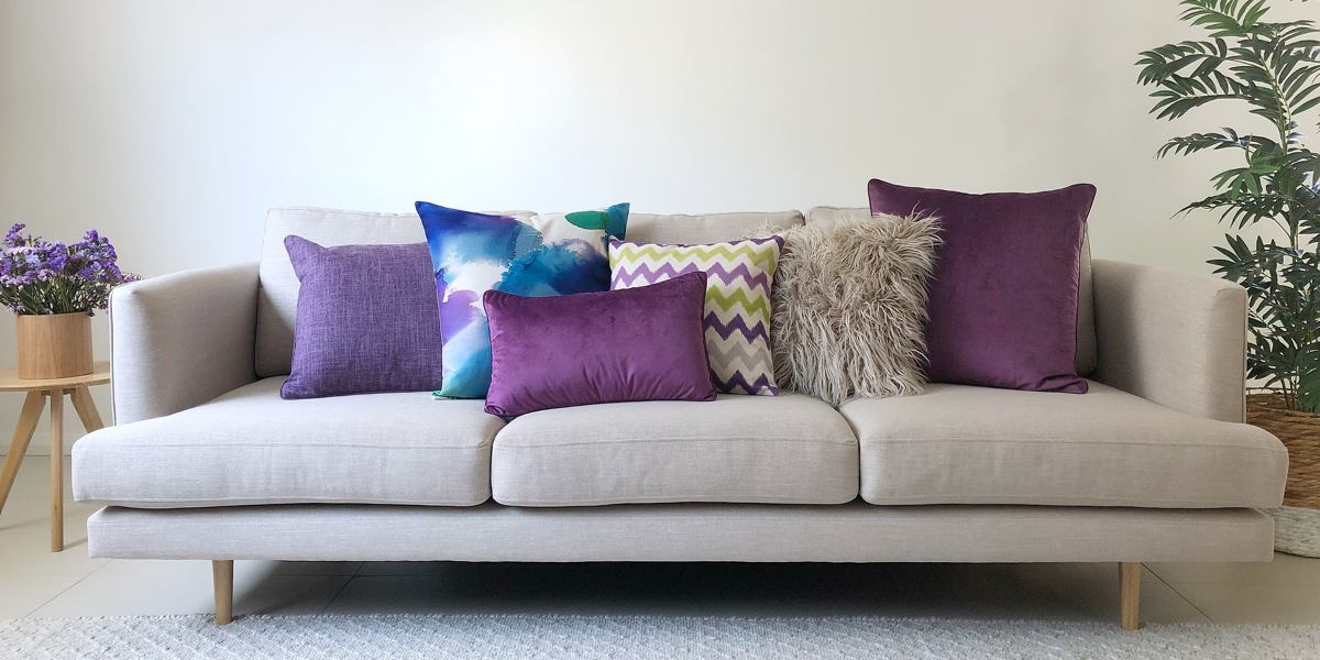 A gret sofa with purple and blue cushions in all different shapes and sizes