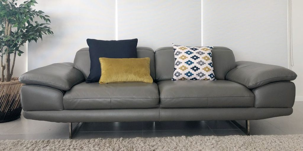 Lounge room with a grey sofa and mustard, navy and print cushion