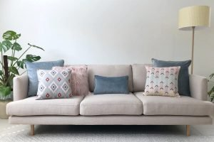 Grey sofa with pastel cushions in pink, grey and blue