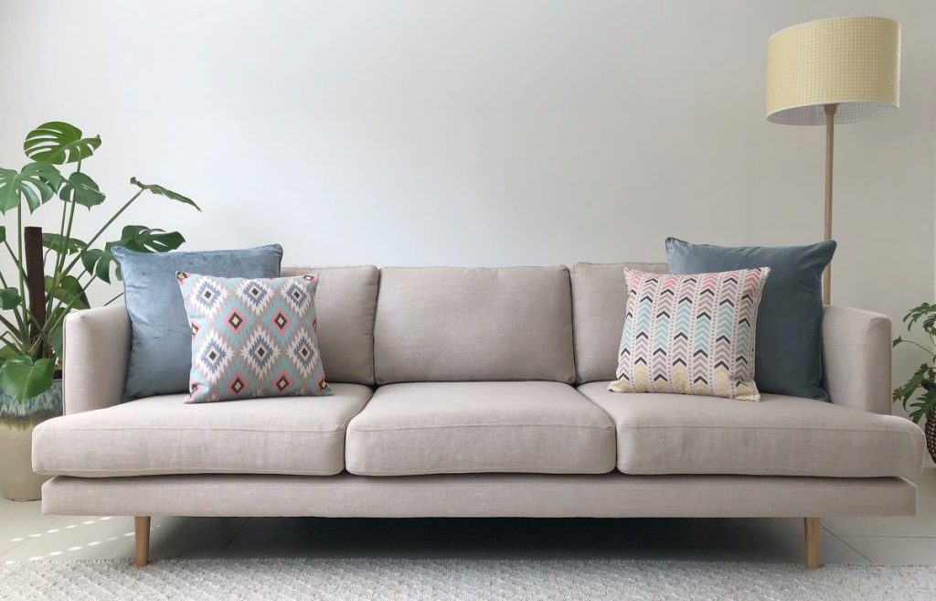 Beige sofa with two large solid blue cushions and two smaller print cushion in pastel colours